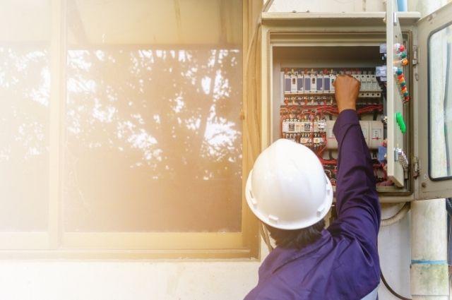 electrician checking circuit breaker